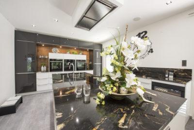 Exklusive Einbauküche mit angrenzendem Massivholz-Esstisch